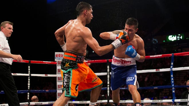 Britain's Amir Khan,  left, lands a punch on his way to a points win against Mexico's Julio Diaz during their welterweight fight in Sheffield, England'