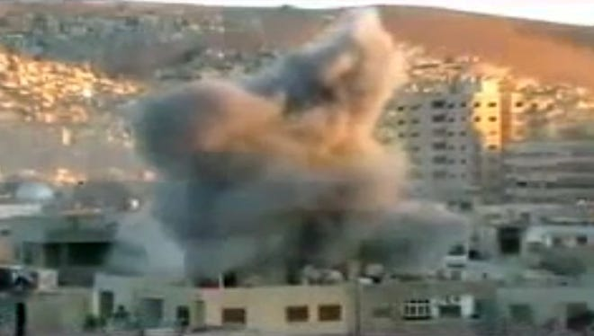 A video image shows an explosion during heavy fighting between rebels and Syrian government forces in the Barzeh district of Damascus on Friday.