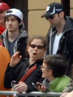 This photo provided by Bob Leonard shows bombing suspects Tamerlan Tsarnaev, 26, center right in black hat, and his brother, Dzhokhar A. Tsarnaev, 19, center left in white hat, approximately 10-20 minutes before the blasts that struck the Boston Marathon.