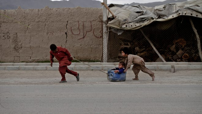 Afghan boys play on a road on the outskirts of Kabul, Afghanistan, April 29, 2013.