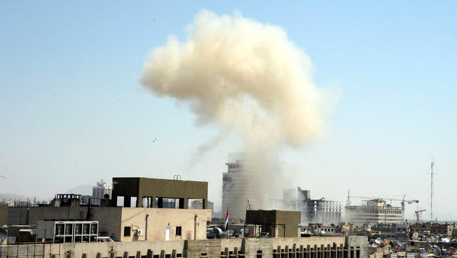 This photo released by the Syrian official news agency, SANA, shows billowing smoke from a powerful explosion that shook Damascus in the central Marjeh district of Damascus, Syria, Tuesday, April. 30, 2013.