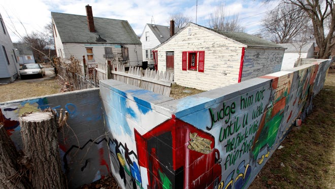 A section of a half-mile long concrete wall, six feet tall and a foot or so thick, now covered with murals, built in the 1940s is shown in Detroit.
