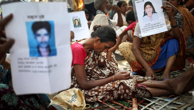 A woman grieves while others hold up pictures of their missing relatives at a school-turned-morgue where family members come to identify and claim bodies found in the garment factory building collapse Thursday in Savar, near Dhaka, Bangladesh.