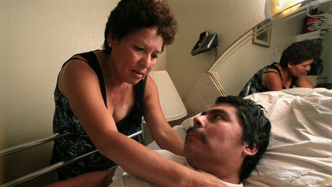 In this Oct. 13, 2008 photo, Lucila Huerta, tends to her husband Guadalupe, who is suffering from Valley Fever and other medical problems, in their apartment in Madera, Calif.