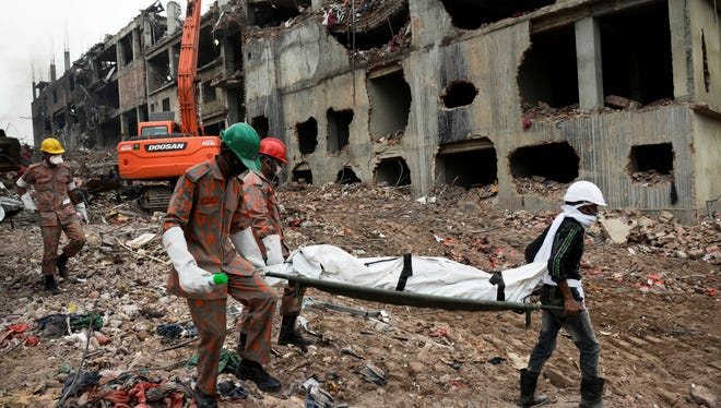 Rescuers carry a body retrieved from the rubble of the eight-story Rana Plaza building that collapsed in Bangladesh.