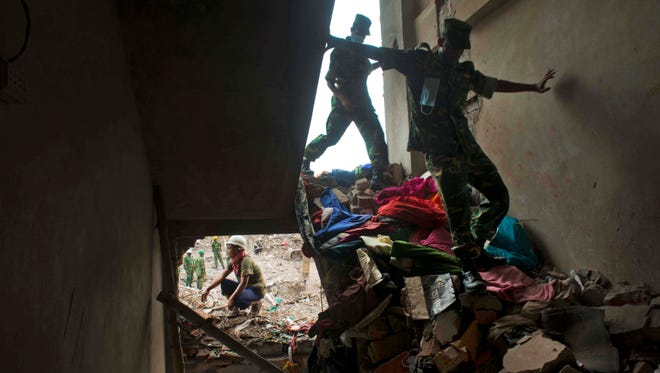 Bangladeshi soldiers walk amid the rubble of the garment factory building that collapsed on April 24 as they continue search operation in Savar, near Dhaka, Bangladesh, on Sunday.