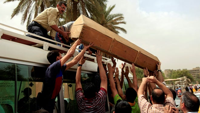 Mourners load the coffin of a man killed in a liquor store attack onto a vehicle in Baghdad on May 15, 2013.