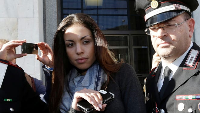 Karima el-Mahroug's is escorted outside the Milan's Law court by two Carabinieri police officers after giving her testimony at the trial of three former Berlusconi aides, in Milan, Italy, Friday.