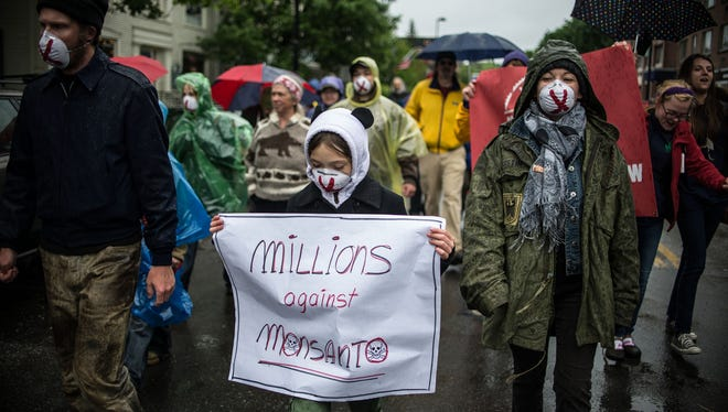 People carry signs during a protest against Monsanto in Montpelier, Vt. on Saturday.