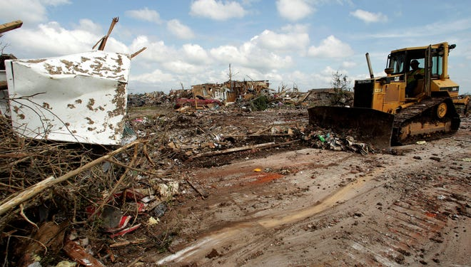 In a May 26, 2013 file photo, Michael Tackett pushes tornado debris to the curb as he helps clean up the home of Brian McAlister, in Moore, Okla.