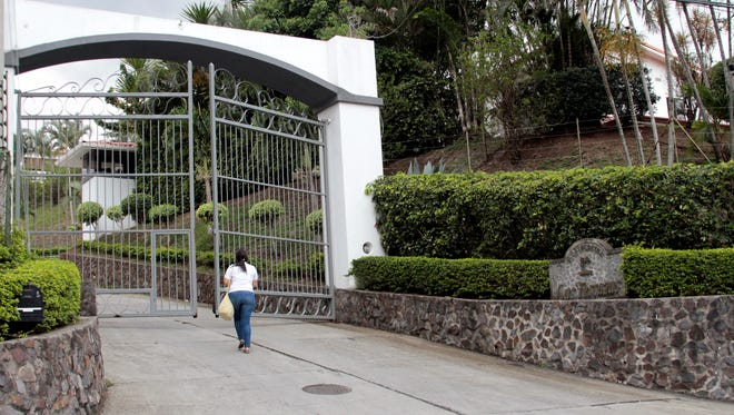 A woman walks toward the entrance to Residencial Las Terrazas in the mountains near Santa Ana, Costa Rica, on May 28, 2013.  Costa Rican police raided one of the residences of Las Terrazas as well as two other homes and five businesses related to Liberty Reserve and seized papers and digital documents that will be turned over to U.S. authorities.