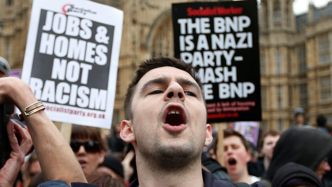 Anti-fascist demonstrators shout slogans against members of the British National Party (BNP), not seen, during a demonstration in central London, Saturday, June 1, 2013. BNP supporters gathered to protest the May 22 killing of British soldier Lee Rigby.