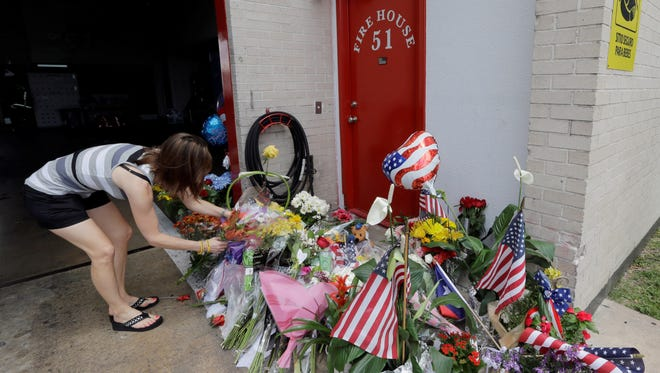 Shannon Neira places flowers at a makeshift memorial at Houston Fire Station 51.