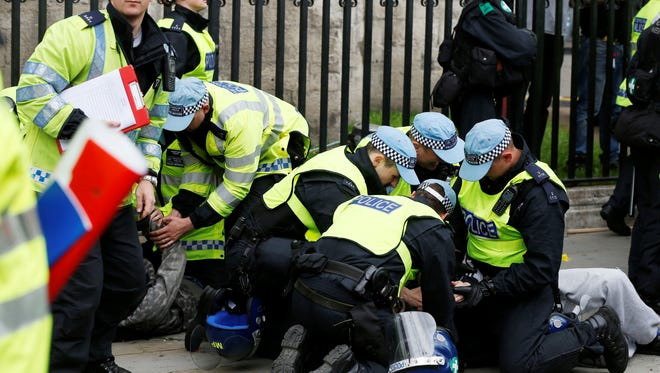 British police officers arrest anti-fascist demonstrators protesting against members of the British National Party.