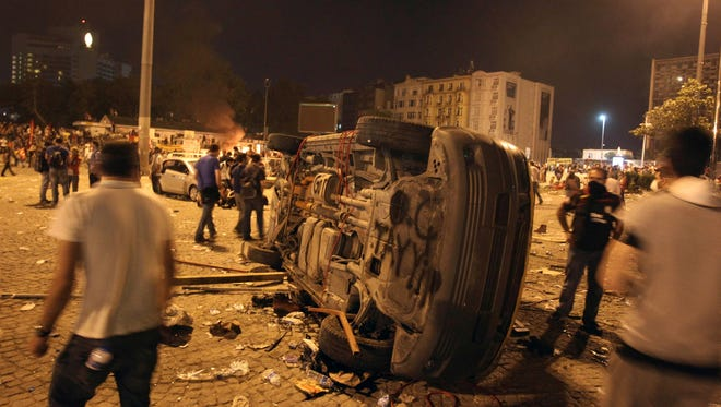 Protesters look at a destroyed car during a rally at Taskim Square in Istanbul early Sunday.