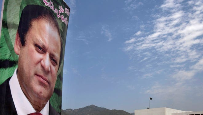 A banner with the portrait of Pakistan's  Prime Minister Nawaz Sharif, is displayed near the National Assembly building, background, in Islamabad, Pakistan, Wednesday, June 5, 2013.