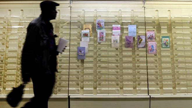 In this April 27, 2013 photo, a man walks past a greeting cards display case in a market in Baltimore. America as a whole has regained all the household wealth it lost to the Great Recession and then some, thanks to higher stock and home prices. (AP Photo/Patrick Semansky)