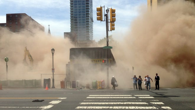 A dust cloud rises as people run from the scene of a building collapse on the edge of downtown Philadelphia on Wednesday.