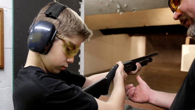 Dan Blackford, right, shows Rory Strain, 12, how to hold a shotgun at a shooting range in Houston.