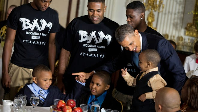 President Barack Obama greets guests, including fathers and their children participants in the Becoming a Man (BAM) program at Hyde Park Academy in Chicago, Friday, June 14, 2013, in the State Dining Room of the White House in Washington, where the president hosted a Father's Day luncheon.