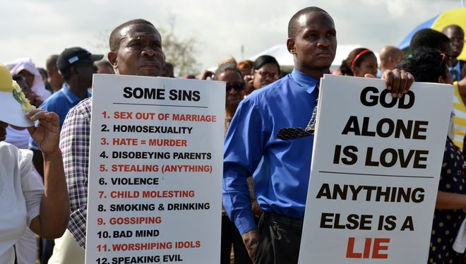 Jamaican churchgoers hold signs while attending an anti-gay rally in Kingston on Sunday.