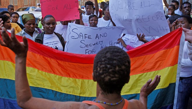 In this May 20, 2010 file photo, women protest against a sentence of 14 years in prison, with hard labor, given to two men in Malawi under Malawi's anti-gay legislation, in the city of  Cape Town, South Africa, Thursday, May 20, 2010. The U.S. embassy in Abidjan made history in June 2013 by hosting a gay pride reception attended by about two dozen openly gay Ivorians.