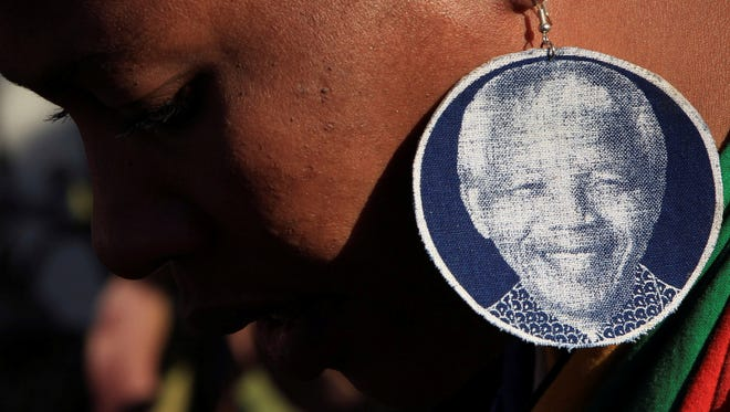 An unidentified woman wears earrings bearing the image of  former South African President Nelson Mandela.