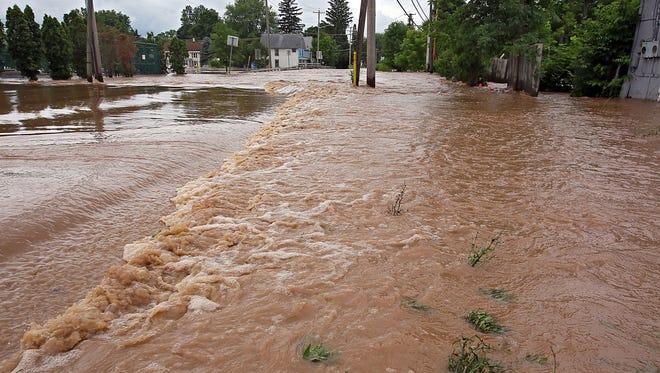 Water flows along Sconondoa Road in Oneida, N.Y., Friday.
