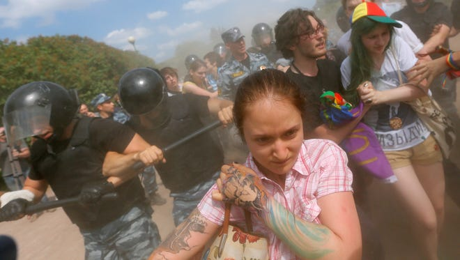 Riot police (OMON) officers detain gay rights activists during their authorized rally in St.Petersburg, Russia, Saturday.