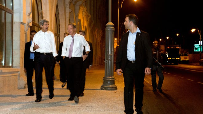 Escorted by security, Secretary of State John Kerry, left, walks with Frank Lowenstein, senior advisor to the secretary on Middle East issues, through the streets of Jerusalem on Sunday.