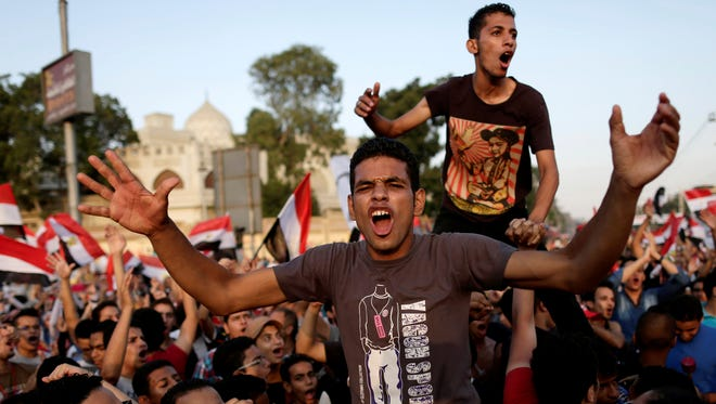 Opponents of Egypt's Islamist President Morsi chant slogans during a protest outside the presidential palace in Cairo.