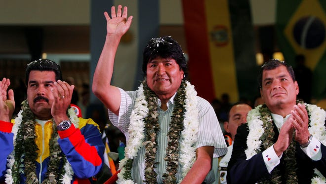 Venezuela's President Nicolas Maduro, left, Ecuador's President Rafael Correa, right, and Bolivia's President Evo Morales acknowledge supporters during a welcome ceremony for presidents attending an extraordinary meeting in Cochabamba, Bolivia, Thursday.