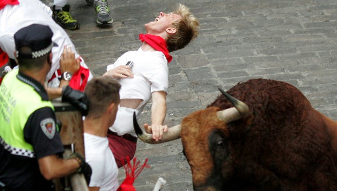 """A runner is gored by an """"El Pilar"""" fighting bull during the running of the bulls at the San Fermin festival, in Pamplona, Spain, Friday, July 12, 2013."""