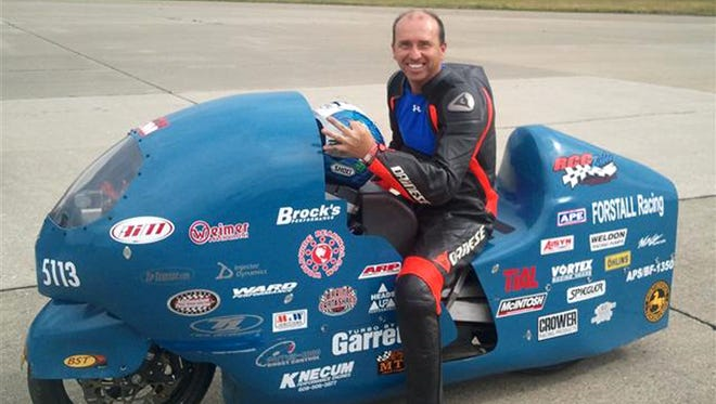 In this 2011 photo provided by the Loring Timing Association, Bill Warner, 44, of Wimauma, Fla., holds his helmet while sitting on a motorcycle.