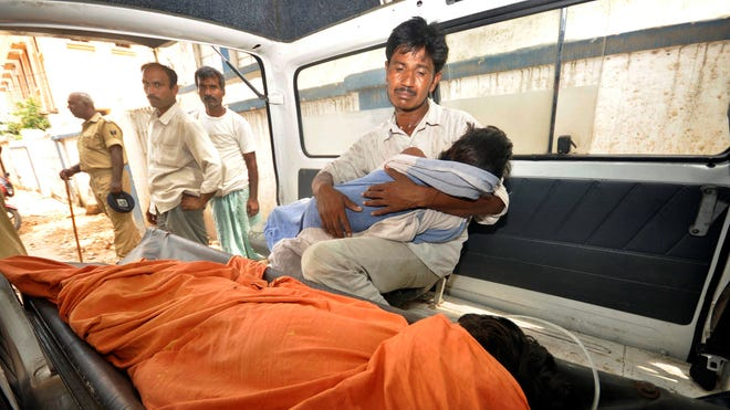 An Indian man mourns as he holds his dead daughter inside an ambulance, outside a hospital in the eastern Indian state of Bihar on Wednesday.