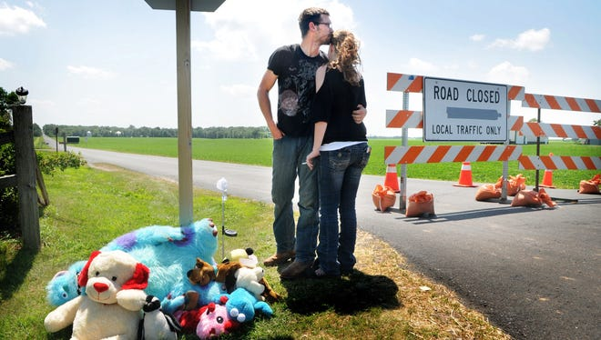 Adam Pool hugs his wife Charlene Shepherd after they put a stuffed puppy dog and candy at a memorial for Isaiah Theis on 180th Street in Centuria, Wis. Thursday July 18, 2013.  The body of Theis, a two-year-old who went missing Tuesday night, was found late Wednesday night in the trunk of a car nearby. Pool and his wife are from Williston, N.D. but were in Centuria on vacation and were among the many volunteers who helped with the search.