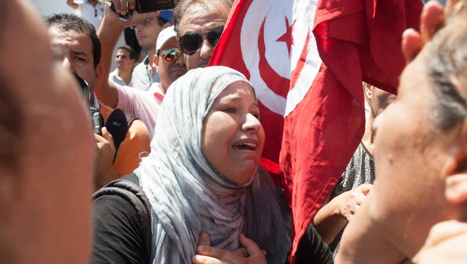 A Tunisian supporter of the Popular Front party reacts after Mohammed Brahmi was shot to death.