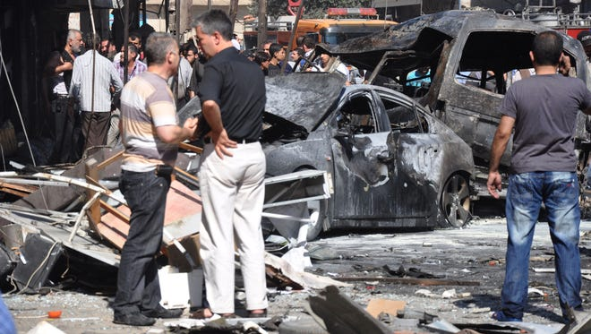In this photo released by the Syrian official news agency SANA, Syrian citizens gather near damaged cars that were burned after a car bomb exploded in the suburb of Jaramana, Damascus, Syria, Thursday.