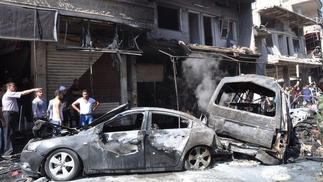 Syrian citizens gather near damaged cars that were burned after a car bomb exploded in the suburb of Jaramana, Damascus, Syria, on July 25, 2013.
