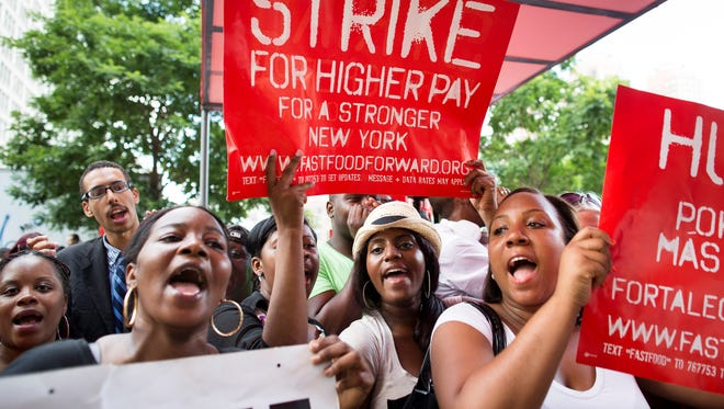 Demonstrators in support of fast food workers protest outside a NYC McDonald's as they demand higher wages and the right to form a union without retaliation on Monday.