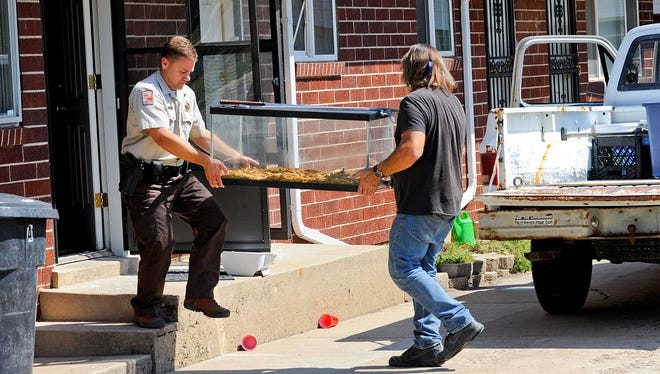 Department of Natural Resourcess David Beveridge and snake handler James Dix removes snake terrariums after a house fire, in Clearfield, Utah. Firefighters discovered 28 snakes Friday at a Clearfield duplex when they responded to a kitchen fire.