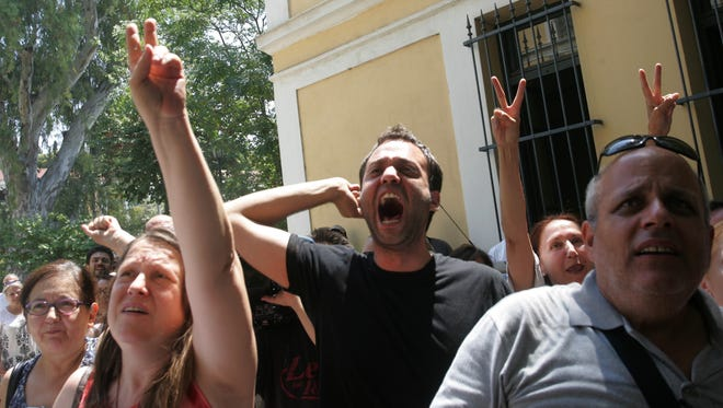 Supporters of protesters arrested during an anti-government demonstration on the outskirts of Athens where TV transmitters are located, shout slogans outside the court in Greek capital on Tuesday. It was latest protest in the wake of a decision by Greece's conservative-led government to shut down state broadcaster ERT in June, to open a new public TV and radio station with fewer staff later this year.