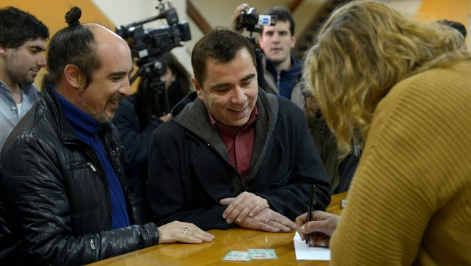 Rodrigo Borda, left, and his partner Sergio Miranda watch a Civil Registry worker take down their information to apply to get married in Montevideo, Uruguay on Monday.