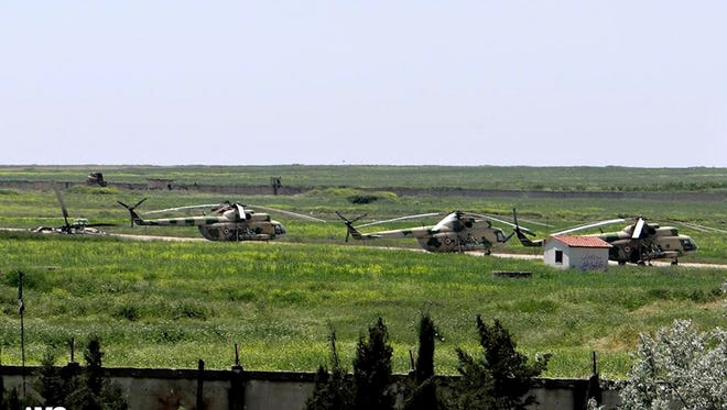 In this June 18, 2013  image provided by Aleppo Media Center AMC which has been authenticated based on its contents and other AP reporting, shows Syrian military helicopters at Mannagh air base in Aleppo province, Syria.