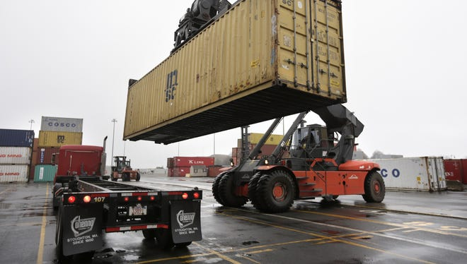 A reach stacker operated by a longshoreman places a shipping container on a truck at the Port of Boston.