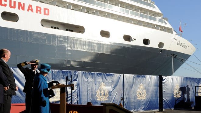 Queen Elizabeth II presses a button to release a bottle of wine against the bow of the Cunard Line ship Queen Elizabeth at the vessel's christening in 2010.