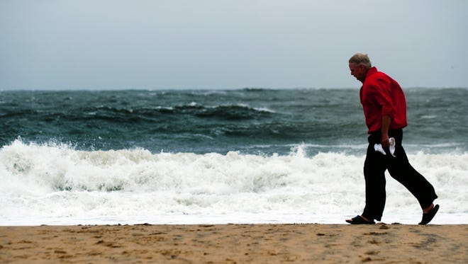 Vacationer Kieth Ashner walks back to his hotel room after watching tidal surge from Hurricane Sandy come ashore at Rehoboth Beach, Delaware, October 28, 2012. Airlines cancelled thousands of flights into and from airports along the US east coast ahead of the arrival of a major storm, officials said Sunday. Air France and other European airlines cancelled all flights into New York and Washington on Monday while US airlines called off thousands of domestic flights and moved planes away from east coast airports away from the path of Hurricane Sandy. New York airports stayed open Sunday but the airport authority warned passengers there will be major disruption in the next two days.                    AFP PHOTO/Jim WATSONJIM WATSON/AFP/Getty Images ORG XMIT: 155047275 ORIG FILE ID: 514942418