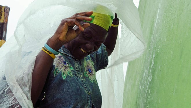 Pauline Daley covers herself in Kingston as Tropical Storm Sandy hit Jamaica last week. Resorts in Ocho Rios took a hit and some are closed till later this week.