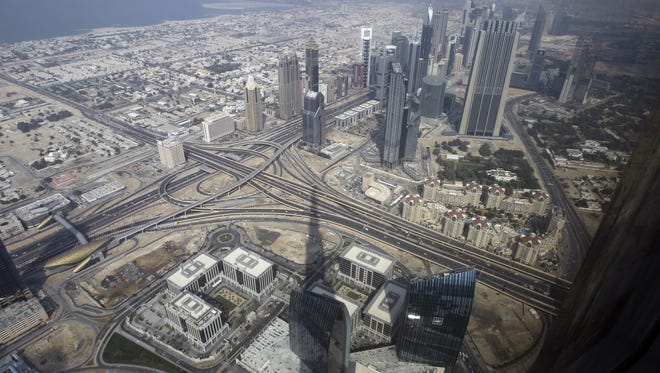 "The shadow of world's tallest building, the Burj Khalifa, is cast on Dubai, as viewed from ""At.mosphere"" the world's highest restaurant, located in the building. Now, officials have announced plans for the world's largest shopping mall, to be built on the outskirts of downtown."