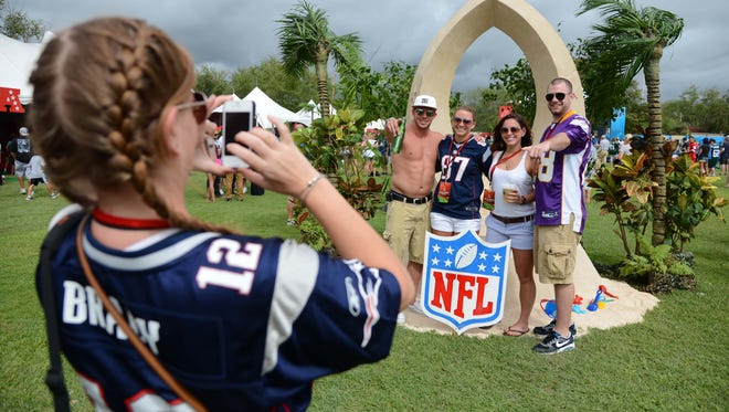 Jill Levine takes a picture of Adam Cordio, left, Kaylin Burke, Melissa Shaw and Phillip Regan in front of a sand sculpture of the Pro Bowl logo during the tailgate party at the 2013 Pro Bowl at Richardson Field.